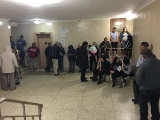 Woodside on the Move tenants gather for a meeting in their building.